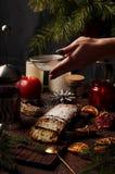 Weihnachtskuchen, in Deutschland christstollen, Frauenhandbesprühen Lizenzfreies Stockfoto