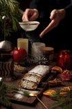 Weihnachtskuchen, in Deutschland christstollen, Frauenhandbesprühen Lizenzfreie Stockfotos