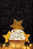 Weihnachtskuchen mit goldenem Stern auf schwarzem Hintergrund Lizenzfreies Stockfoto