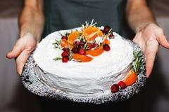 Weihnachtskuchen mit Orangen und Gewürzen in den Händen Stockfoto