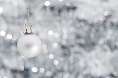 Weihnachtskugel über glänzendem Girlandehintergrund Lizenzfreie Stockfotos
