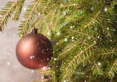 Weihnachtskugel auf einem Weihnachtsbaum Fallende Schneeflocken und Sterne Stockfoto