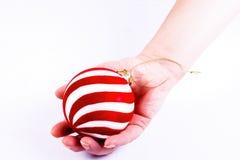 Weihnachtskugel in einer Hand der Frauen stockfoto