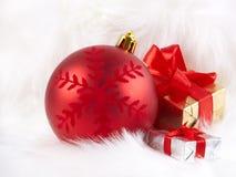 Weihnachtskugel und -kästen auf dem weißen Pelz Stockfoto