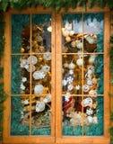 Weihnachtskugel und -verzierung hinter Fenster Lizenzfreie Stockfotografie