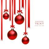 Weihnachtskugeln, die mit Farbbändern auf Weiß hängen Stockfotografie