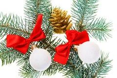 Weihnachtskugeln, Rotbögen und Kegel auf Tanne stockfotografie