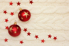 Weihnachtskugeln, -sterne und -korne auf dem Stricken lizenzfreies stockbild