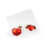 Weihnachtskugeln und Gruß-Karte auf weißem Schnee Lizenzfreies Stockfoto