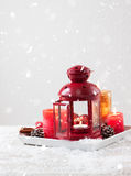 Weihnachtslaterne mit Kerzen, Schnee, Weihnachtsdekorationen und Tannenzapfen Lizenzfreies Stockfoto