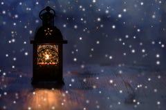Weihnachtslaterne mit Schneeflocken und Sternen auf einem blauen Hintergrund stockfotografie