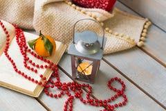 Weihnachtslaternen, Tangerine und rote Perlen auf weißer hölzerner Rückseite Lizenzfreies Stockbild