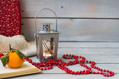 Weihnachtslaternen, Tangerine und rote Perlen auf weißer hölzerner Rückseite Stockbild