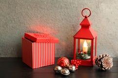 Weihnachtslaternenrot mit Kiefernkegeln der Geschenkboxsilberglocken auch stockfotografie