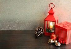 Weihnachtslaternenrot mit Kiefernkegeln der Geschenkboxsilberglocken auch stockfoto