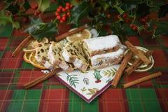 Weihnachtslebensmittel-Fotografiebild mit stollen Kuchenbrotzimtstangeschnittstechpalmenblätter und -beeren auf grünem rotem Küch lizenzfreie stockbilder