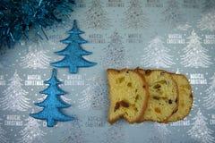 Weihnachtslebensmittel-Fotografiebild mit traditionellem italienischem Panettonekuchen mit blauen Lametta- und Funkelnbaumdekorat Stockfotografie