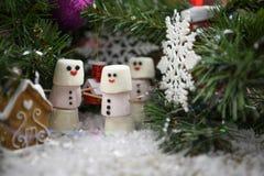 Weihnachtslebensmittel-Fotografiebild von Eibischen in Form des Schneemannes im Schnee unter einem Weihnachtsbaum mit Dekoratione Stockfotografie