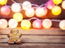 Weihnachtslebensmittel, Lebkuchen-Mann auf einem hölzernen Hintergrund Girlande für das neue Jahr Lizenzfreies Stockbild