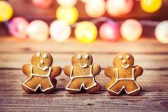 Weihnachtslebensmittel, Lebkuchen-Mann auf einem hölzernen Hintergrund Girlande für das neue Jahr Lizenzfreie Stockfotos