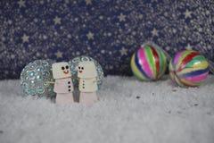 Weihnachtslebensmittelphotographie von den Eibischen geformt als Paarschneemann, der im Schnee mit bunten Flitterdekorationen und Stockfotografie