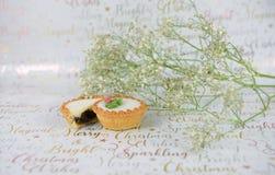 Weihnachtslebensmittelphotographie von weißen grünen Blumen mit Funkeln und zerkleinern Torten auf Weihnachtspackpapierhintergrun Stockbild