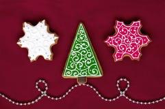 Weihnachtslebkuchen auf rotem Hintergrund lizenzfreie stockfotografie