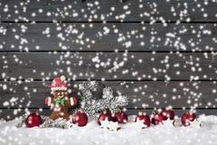 Weihnachtslebkuchenbärnweihnachtsbirnen cinnnamon Stern-Kiefernzweig auf Stapel des Schnees gegen hölzernen Wandschnee fällt Stockbilder