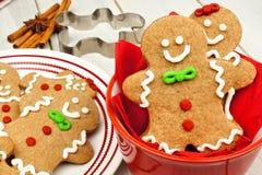 Weihnachtslebkuchenmannplätzchen in der roten Schüssel auf weißem Holz stockfotografie