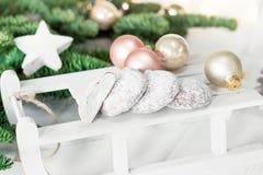 Weihnachtslebkuchenplätzchen auf hölzernem Schlitten- und Tannenbaum Lizenzfreie Stockfotografie