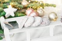 Weihnachtslebkuchenplätzchen auf hölzernem Schlitten- und Tannenbaum Stockfotos