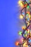 Weihnachtslichter auf blauem Hintergrund mit Kopienraum Lizenzfreies Stockbild