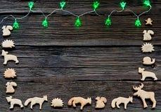 Weihnachtslichter auf einem hölzernen Hintergrund mit freiem Raum Lebkuchen in Form der Tiere, der Sterne und der Herzen Stockfotografie