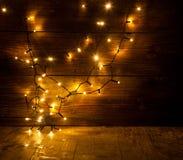 Weihnachtslichter auf hölzernem Hintergrund Stockfotografie