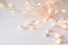 Weihnachtslichter, die auf einem weißen hölzernen Hintergrund brennen Lizenzfreies Stockbild