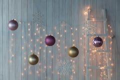 Weihnachtslichter, die auf einem weißen hölzernen Hintergrund brennen Stockbilder
