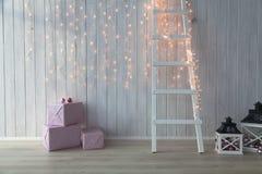 Weihnachtslichter, die auf einem weißen hölzernen Hintergrund mit rosa giftboxes und Treppe brennen Stockbild