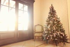 Weihnachtslichter, die in einem Baum in einem Restaurantraum-Gelbrosa hängen Stockfotografie