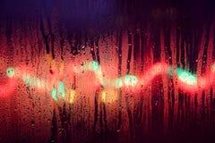 Weihnachtslichter hinter einem regnerischen Fenster Lizenzfreie Stockfotografie