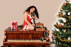Weihnachtsmädchen auf Klavier, wenn dem Baum und Geschenke, in Sankt verziert sind stockfoto