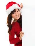 Weihnachtsmädchen, das von hinten leere Zeichenanschlagtafel späht. Stockfotos
