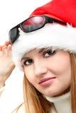 Weihnachtsmädchen in den Sankt-Hut- und Sonnegläsern Stockfotografie