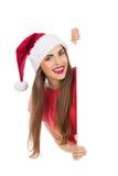 Weihnachtsmädchen hinter einem Plakat Stockbilder