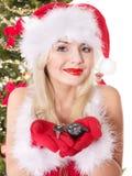 Weihnachtsmädchen im Sankt-Hut, der Selbsttasten anhält. Stockfoto