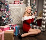 Weihnachtsmädchen mit den Geschenken, die nahe Spiegel- und Farbenlippen mit Lippenstift sitzen Frau gekleidet als Sankt Stockfoto