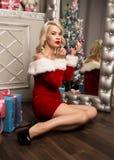 Weihnachtsmädchen mit den Geschenken, die nahe Spiegel- und Farbenlippen mit Lippenstift sitzen Frau gekleidet als Sankt Lizenzfreie Stockfotografie