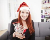 Weihnachtsmädchen mit Minieinkaufslaufkatzenwarenkorb Stockbilder
