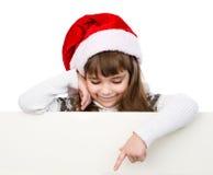Weihnachtsmädchen mit Sankt-Hut, der hinter weißem Brett steht Stockbilder