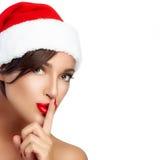 Weihnachtsmädchen in Santa Hat, die ein Stille-Zeichen tut Stockfotos