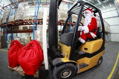 Weihnachtsmann als Gabelstaplerbediener bei der Arbeit in den Waren lizenzfreie stockbilder